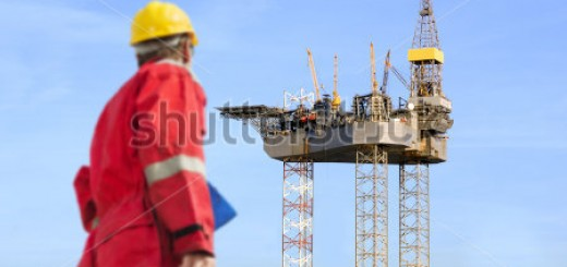 stock-photo-roughneck-out-of-focus-looking-at-a-huge-oil-rig-being-constructed-112219793